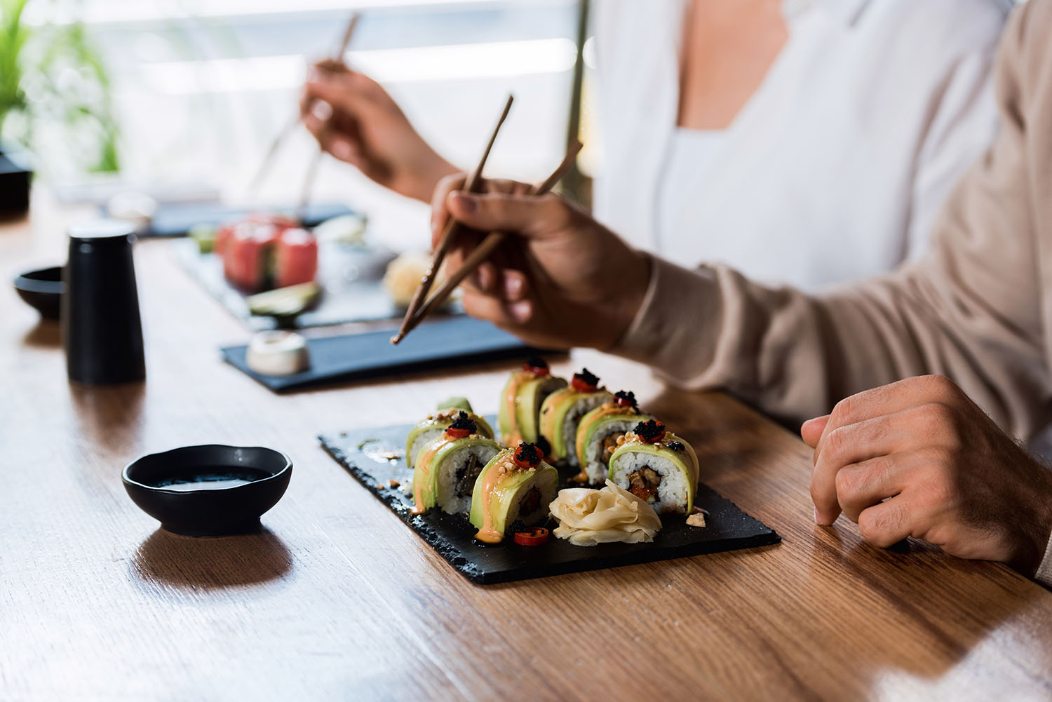 A couple eating sushi at a restaurant.