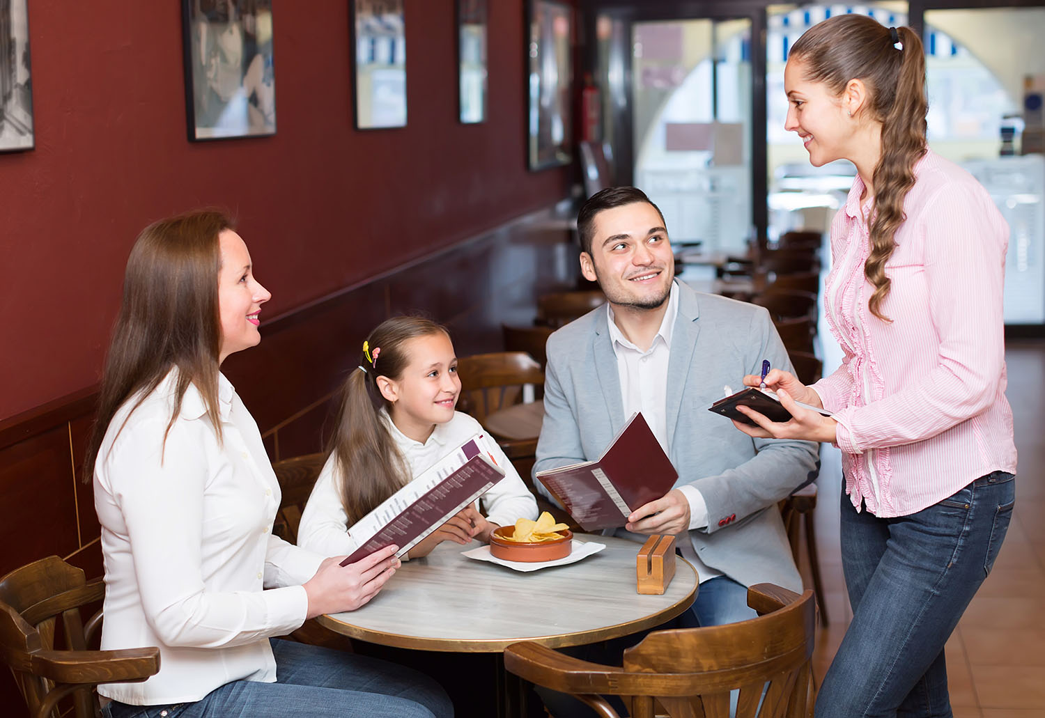 Smiling waitress taking an order from a family of 4 in a restaurant.