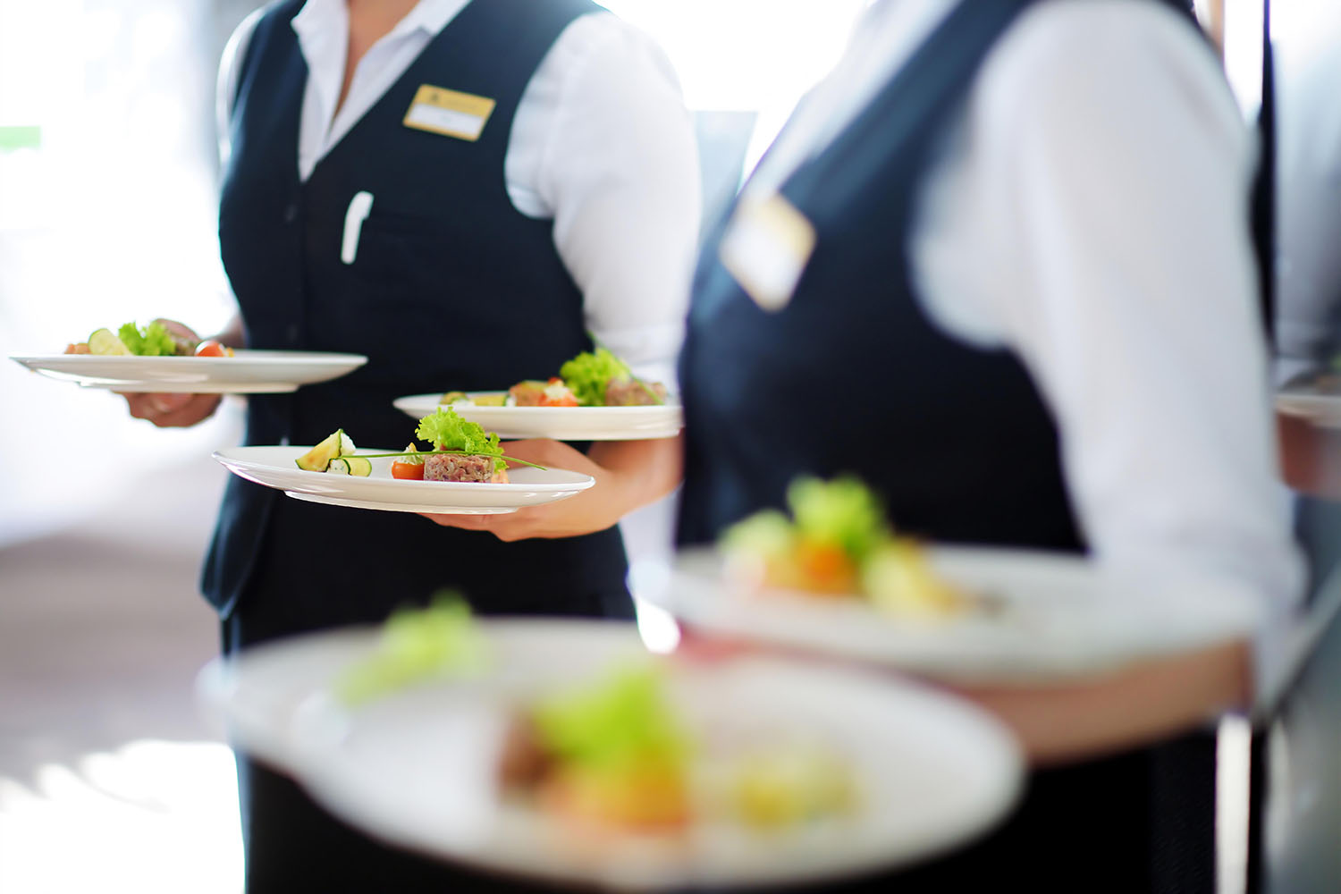 Two servers delivering plates of food to the table.